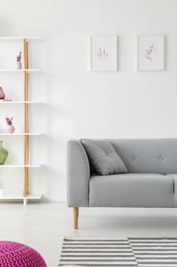 Vertical view of scandinavian living room design with grey couch, heater prints on the wall and wooden shelf with vases on it, real photo with mockup