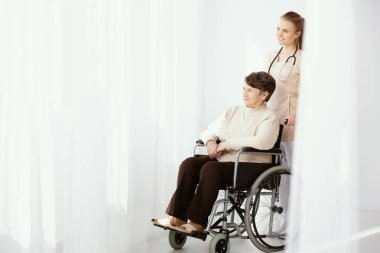 Smiling caregiver supporting paralysed elderly woman in the wheelchair next to copy space