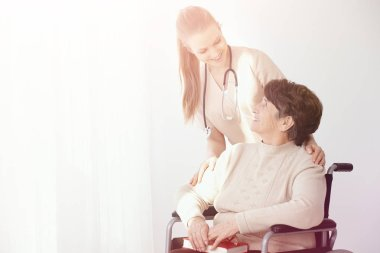 Smiling nurse supporting paralysed elderly woman in the wheelchair next to copy space