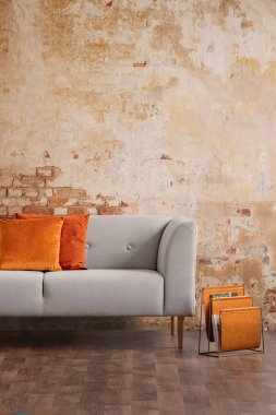 Orange cushions on grey sofa against red brick wall in modern living room interior. Real photo