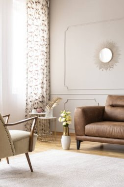 Real photo of bright living room interior with white carpet, window with curtains and fresh roses in vase placed by leather brown sofa
