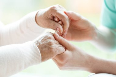 Closeup of the hands of a young woman holding hands of an elderly lady