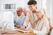 Usmíval se starší paní pomáhá její přítel během počítačových tříd pro seniory univerzity třetího věku