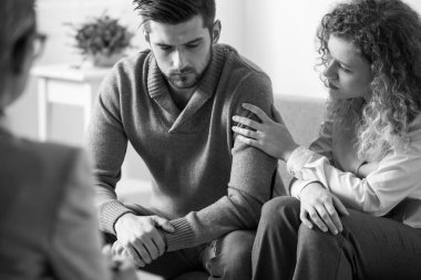 Black and white photo of supportive wife touching husband's arm during psychotherapy session for married people with problems
