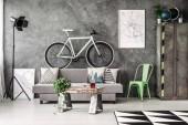 Fotografie dunkles Industrie-Wohnzimmer mit grauer Couch und weißem Fahrrad