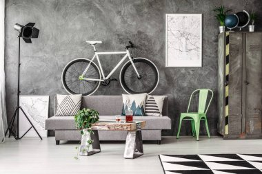 Dark industrial living room with grey couch and white bike stock vector