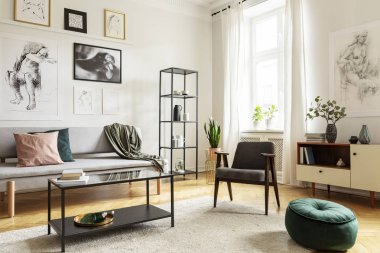 Pouf next to armchair in living room interior with table in front of sofa under posters. Real photo