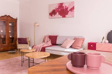 Closeup of two coffee cups on the table in elegant living room with grey couch with pastel pink pillows, stylish armchair and vintage cabinet
