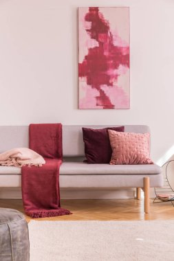 Poster above grey settee with red blanket and cushions in bright living room interior. Real photo
