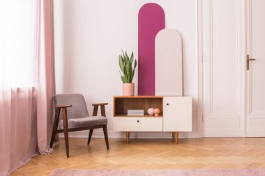 Grey wooden armchair next to cabinet with plant in white and pink living room interior. Real photo