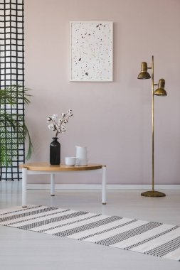 Flowers on wooden table next to gold lamp in living room interior with poster and rug. Real photo