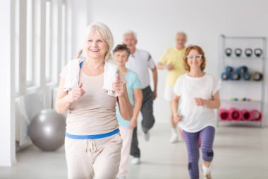 Happy active senior woman with towel exercising during physical classes for elderly people