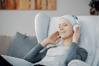 Peaceful woman with headphones and blue headscarf sitting in comfortable armchair resting at home after chemotherapy