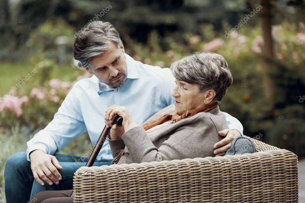 Sad grey senior lady with walking cane sitting in the garden with her son