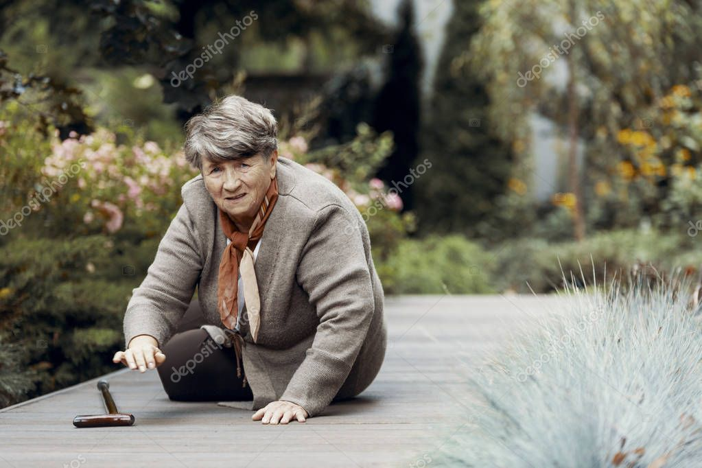Grey elderly lady lies on the ground in the park