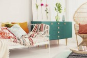 Fotografie Green cabinet with crown shape handle in the middle of bright bedroom with colorful bedding on the bed and rattan peacock chair with pillow