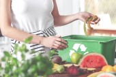 Closeup of eco friendly woman in the kitchen disposing of leftovers of kiwi into compost bin while preparing fruit salad