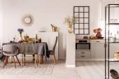 Stylový otevřenou kuchyň a jídelna interiér s bílou skříň a dlouhý stůl s šedou ubrus a jídlo