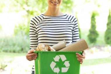 Beautiful smiling woman with green recycling container with paper waste