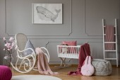 Flowers and rocking chair in grey babys bedroom interior with poster and pouf. Real photo