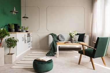 Open book on dark green velvet pouf in grey living room and kitchen interior with retro armchair, coffee table and sofa