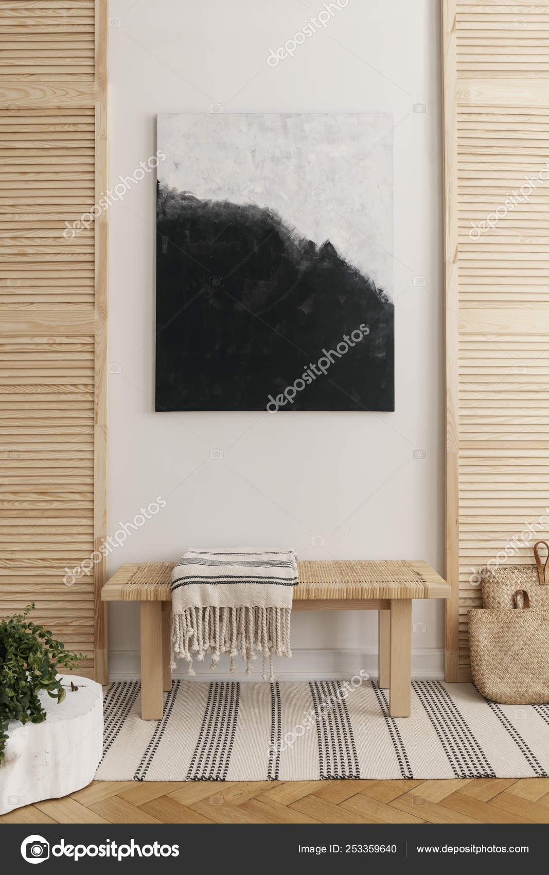 Black And White Painting Above Wooden Bench With Striped Blanket In