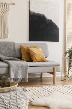 Vertical view of white handmade macrame and modern painting on wall of trendy living room interior with grey stylish couch with yellow pillows and warm blanket