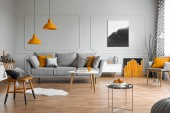Photo Orange accents in a grey living room interior