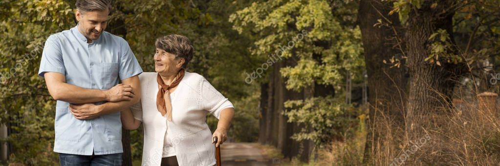 Panoramic view of grey senior lady with walking cane in the garden with volunteer