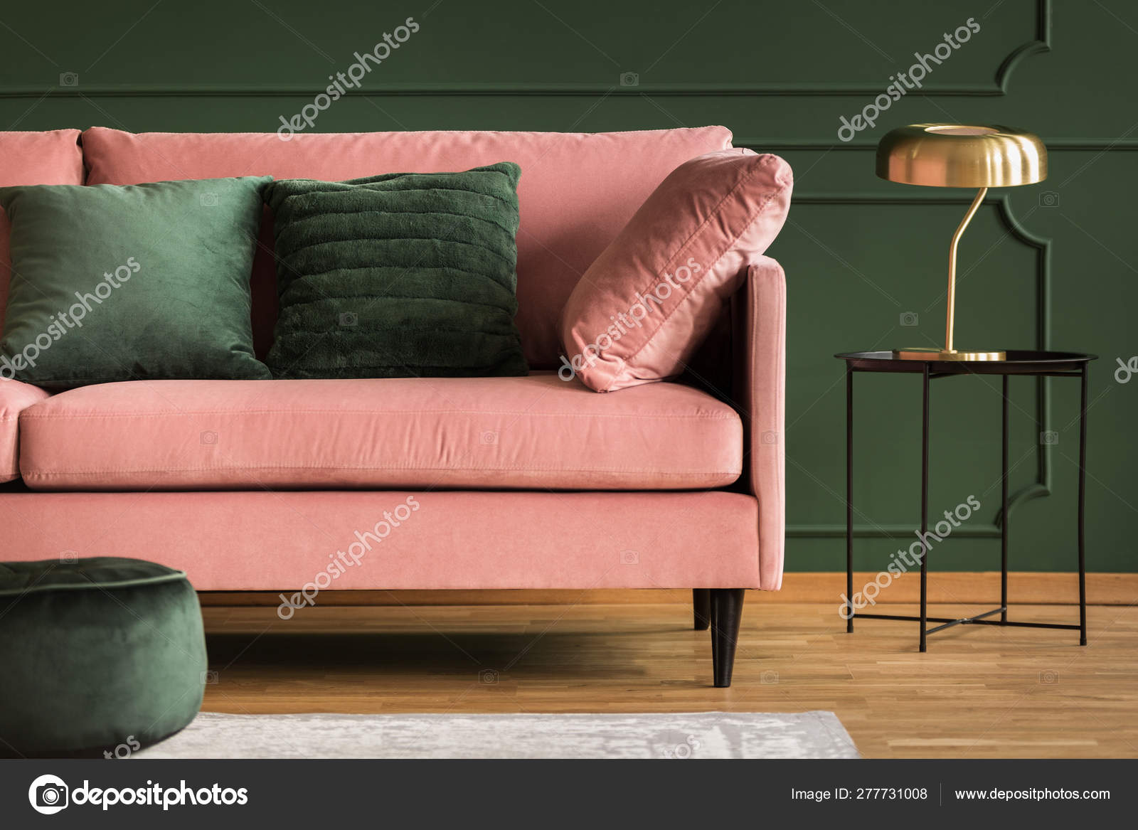 Powder pink sofa and golden lamp in a dark green living room ...