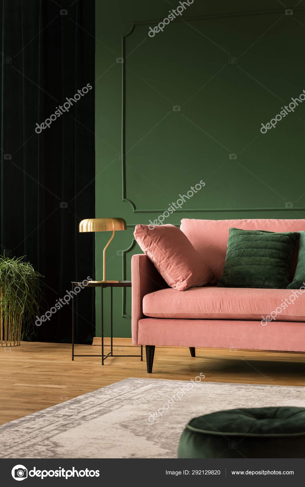 Stylish golden lamp on industrial table next to pink couch ...