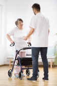 Photo Senior woman with walker and young physiotherapist during session