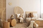 Photo Wicker peacock chair with pillow, armchair and toy in beige and wooden baby bedroom interior