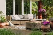 Klasický nábytek na dřevěné terase v zelené krásné zahradě