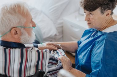 Senior worried woman talking to her sick husband with oxygen mask
