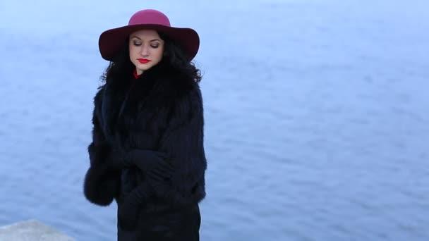 Úžasná žena v červeném klobouku na pozadí vody