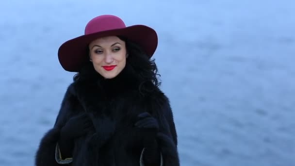 Amazing woman in a red hat on the background of water