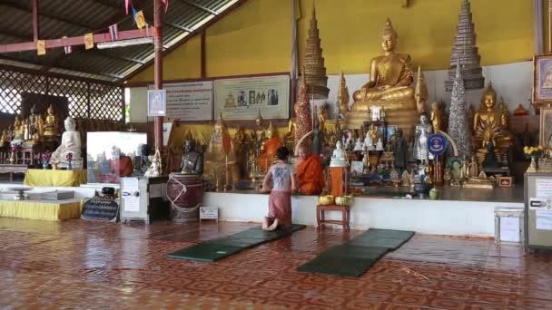 Thailandia, Phuket, 2018 Un monaco benedice e lega un amuleto stringa sulla mano di una ragazza in un tempio buddista