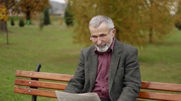 Handsome grandfather with a beautiful beard in a gray jacket sits on a bench in the park and reads a newspaper