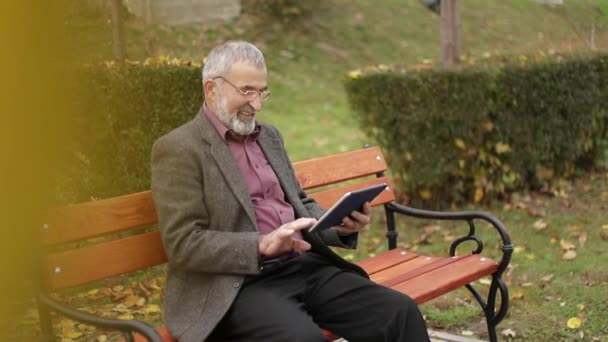Grandpa use a tablet sitting in the park on the bench