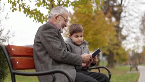Grandpa and his grandson spend time together in the park. They are sitting on the bench and use the tablet