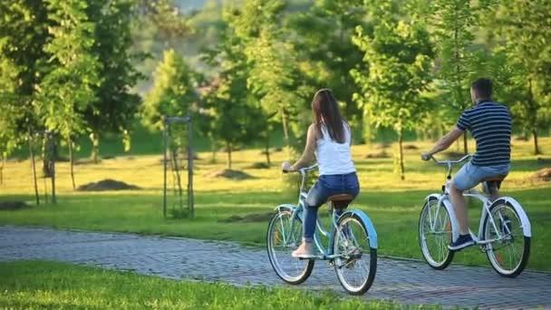 Boldog pár lovaglás kerékpár a parkban. nyári idő. naplemente