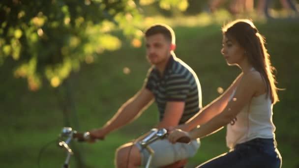 Boldog fiatal pár élvezi a kerékpár út. Napsütéses nyári idő.