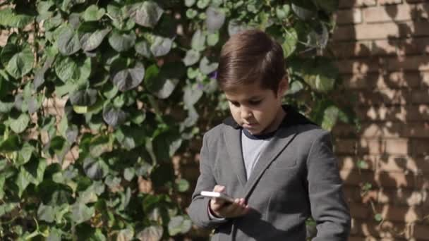 Cute little Boy in jacket use his phone. Background of ivy wall