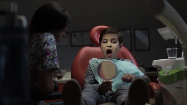 Female dentist in work. Patient child boy in dental clinic