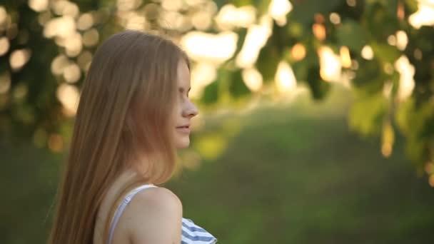 Krásná dívka nakreslí obrázek v parku pomocí palety barvy a stěrky. Malířský stojan a plátno s obrázkem. Léto je slunečný den, slunce.