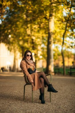 A young girl in a brown coat sits in the middle of the park on a khaki stool
