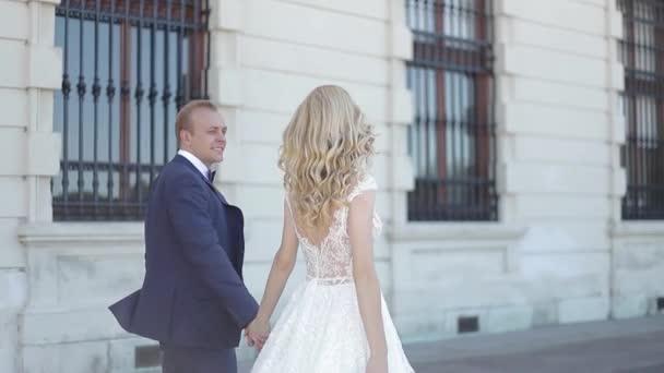 Pár chůze u velkého paláce. Elegantní ženich a nevěsta ve svých svatebních šatů. Láska