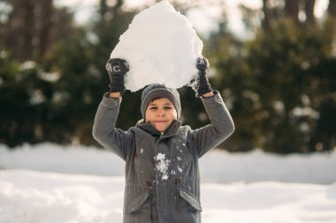 Little Boy play with snow. He take a snowballs and play
