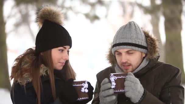 Mladý pár v pohádkovou zimu je ohřátý teplý nápoj. Vánoční nálada